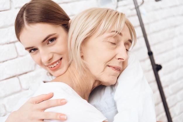 Niña y anciana abrazando en el hospital juntos.