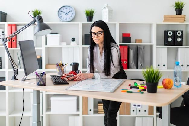 Una niña con anteojos se para cerca de la mesa, sostiene un rotulador en la mano e imprime en el teclado.