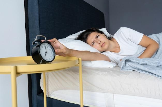 La niña apaga el molesto despertador para seguir durmiendo. duerme un poco más. es una mañana difícil. hora de despertar.