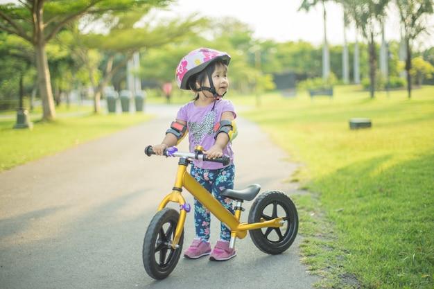 Niña aprende a montar bicicleta de equilibrio en el parque