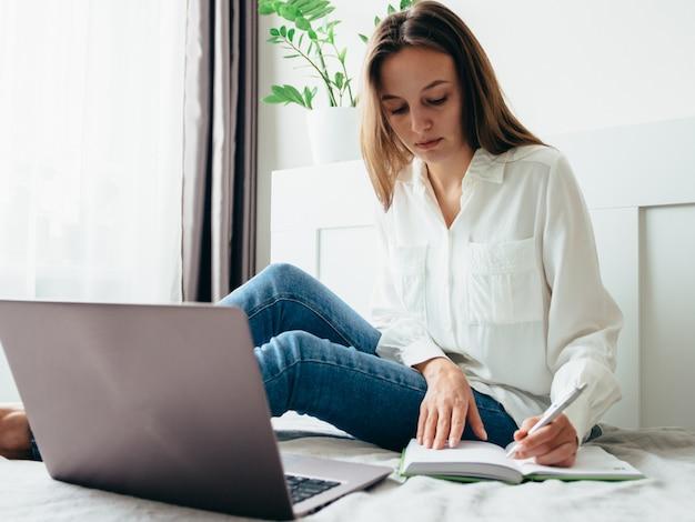 La niña aprende, trabaja, se desarrolla en línea mientras está sentada en casa