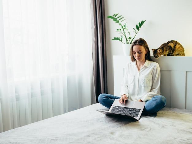 La niña aprende, trabaja, se desarrolla por sí misma en línea mientras está sentada en casa frente a un gato.