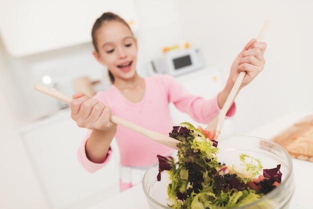 La niña está aprendiendo a preparar una ensalada en una cocina ligera.