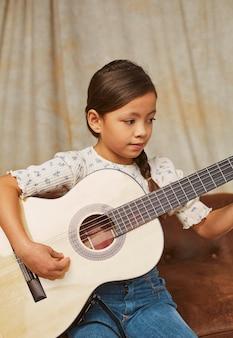 Niña aprendiendo a tocar la guitarra en casa