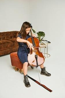 Niña aprendiendo a tocar el violonchelo en casa