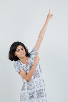 Niña apuntando hacia arriba en camiseta, delantal y mirando confiada