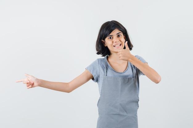 Niña apuntando a un lado, mostrando el pulgar hacia arriba en camiseta, delantal y mirando alegre, vista frontal.