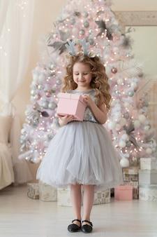 Niña en aro con astas de ciervo, con caja de regalo cerca del árbol de navidad blanco.
