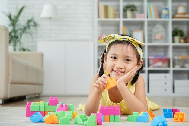 Niña asiática acostada en el piso en casa y jugando con coloridos bloques de construcción