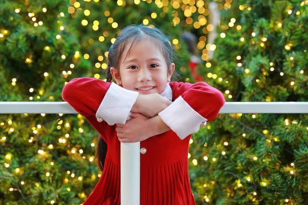 Niña asiática alegre en el vestido rojo que se divierte en la estación del invierno y festival de la feliz año nuevo contra fondo de la navidad.