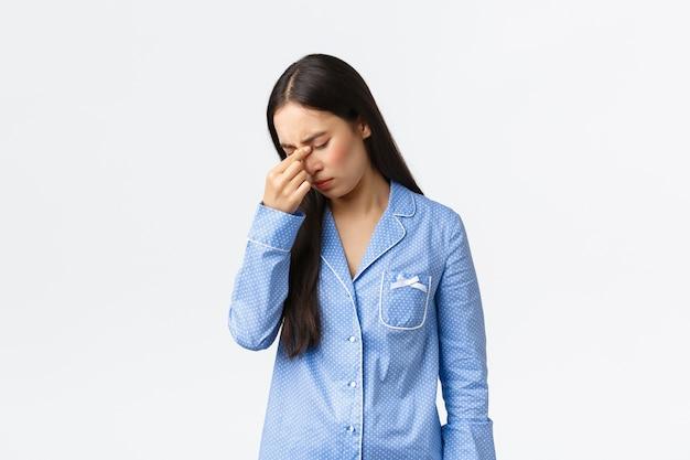 La niña asiática angustiada y agotada se siente mal, en pijama no puede dormir por la noche, frotarse los ojos cerrados, tener insomnio, estar de pie mal con dolor de cabeza, se enfermó sobre fondo blanco.