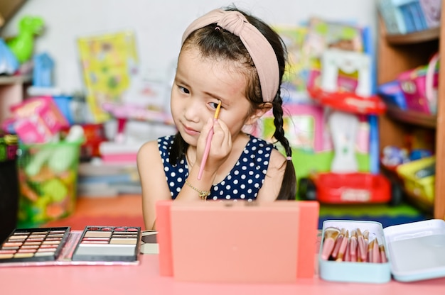 Niña asiática aplica maquillaje de cejas con cosméticos de madre en casa
