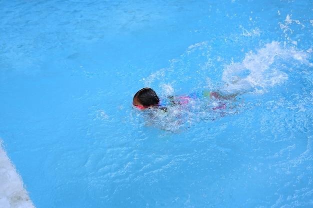 Niña asiática aprendiendo a nadar en la piscina. colegiala practicando natación.