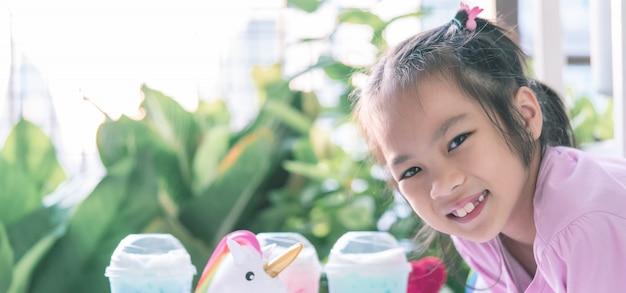 Niña asiática está bebiendo leche de unicornio