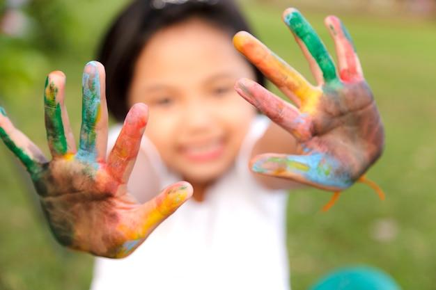 Niña asiática con las manos pintadas en pinturas de colores
