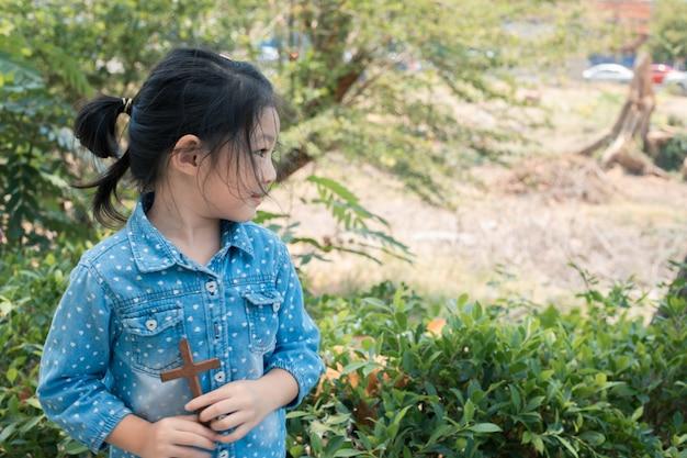 Niña asiática con cruz de madera cristiana.