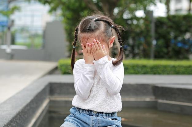 La niña asiática cubre su cara con sus manos