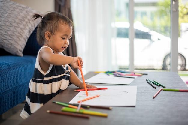 Niña asiática dibujando en una hoja grande de papel blanco