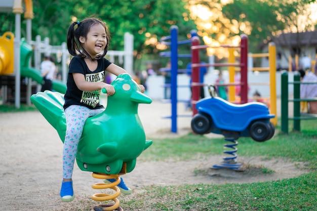 Niña asiática disfruta jugando en un parque infantil
