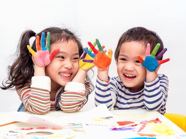 Niña asiática divertida dos que juega las manos de la pintura de la acuarela.