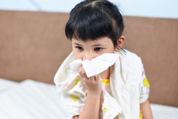 La niña asiática enferma envuelta en un pañuelo se enfría y se suena la nariz durante la temporada de gripe, el niño moquea y estornuda sonándose la nariz y la fiebre en casa