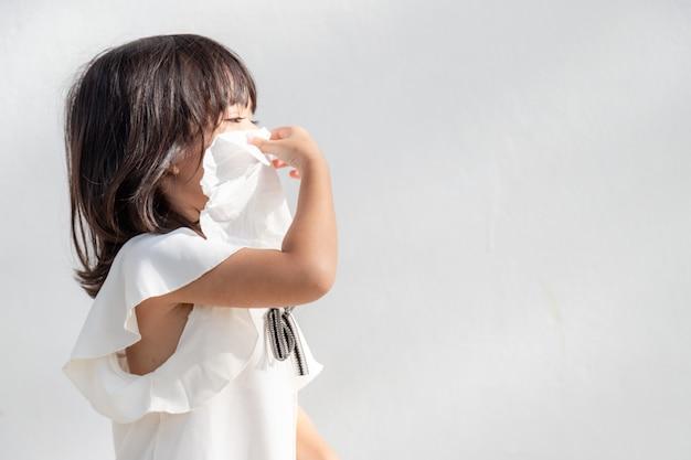 Niña asiática enferma con estornudos en la nariz y tos fría en un pañuelo de papel debido a la debilidad o virus y bacterias del clima de polvo y jardín de infantes y preescolar