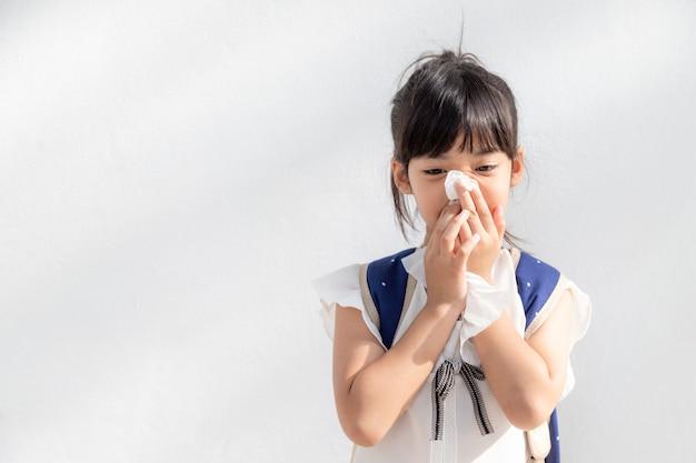 Niña asiática enferma con estornudos en la nariz y tos fría en un pañuelo de papel debido a la debilidad o virus y bacterias del clima polvoriento