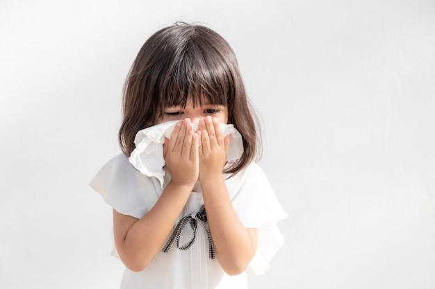 Niña asiática enferma con estornudos en la nariz y tos fría en un pañuelo de papel porque está débil