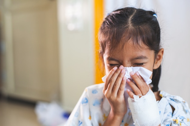 Niña asiática enferma que tiene una solución intravenosa vendada limpiando y limpiando la nariz con un pañuelo en la mano en el hospital
