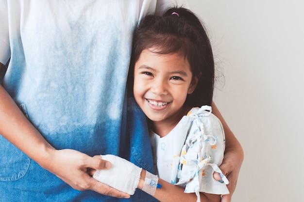 Niña asiática enferma que tiene una solución intravenosa vendada sonriendo y abrazando a su madre en el hospital