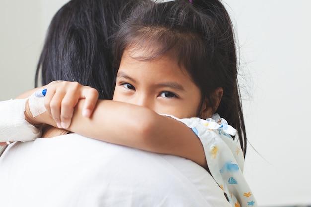 Niña asiática enferma que tiene una solución iv vendada abrazando a su madre con amor en el hospital