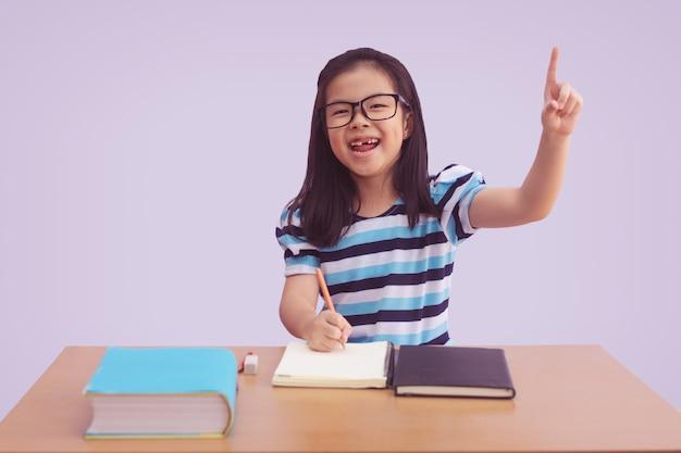 Niña asiática escribiendo un libro sobre la mesa. mostrando el dedo índice hacia arriba con la boca abierta, aislado sobre fondo gris