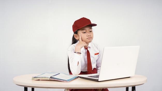 Niña asiática de la escuela primaria en busca de ideas en la pantalla de su portátil aislado sobre fondo blanco.