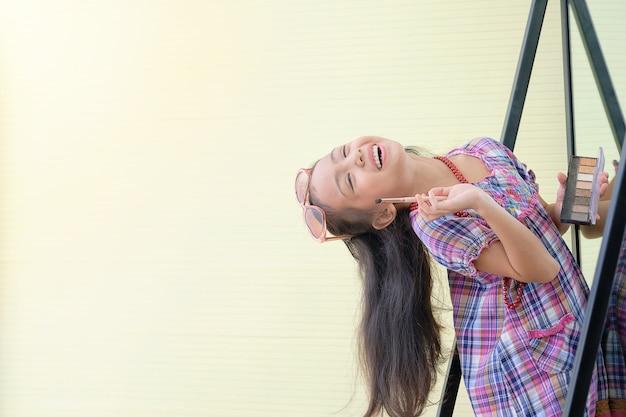 Niña asiática está feliz con maquillaje frente al espejo