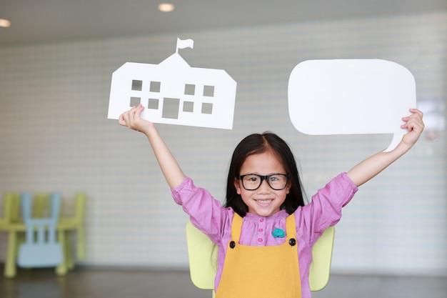 La niña asiática feliz en los overoles rosa-amarillos que sostienen la escuela de papel de la maqueta y vacia la burbuja en blanco del discurso para decir algo en sala de clase con mirar derecho. concepto de educación y conversación.