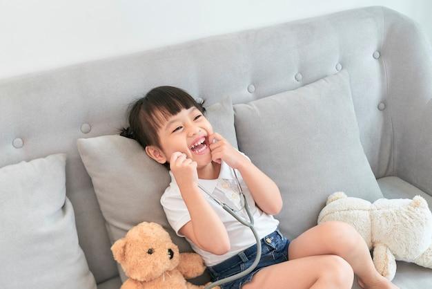 Niña asiática juega con muñeco de juguete