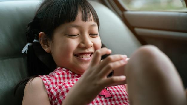 Niña asiática jugando en el teléfono inteligente en el coche