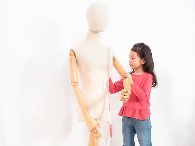 La niña asiática linda de 6 años juega un papel de sastre o diseñador con un maniquí.