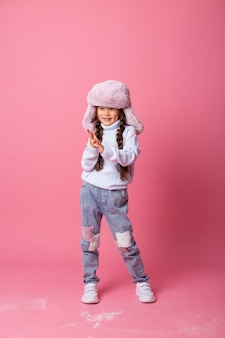 Niña asiática linda en ropa de invierno sopla nieve de las palmas. final de invierno, fondo rosa, espacio para texto