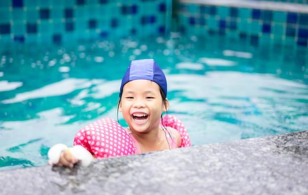 Niña asiática con mangas inflables jugando en la piscina