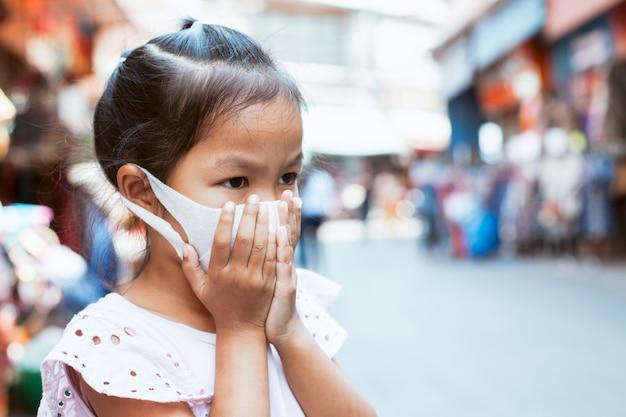 Niña asiática con máscara de protección contra la contaminación del aire smog