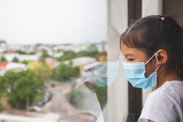 Niña asiática con máscara de protección mirando afuera a través de la ventana y quedarse en casa