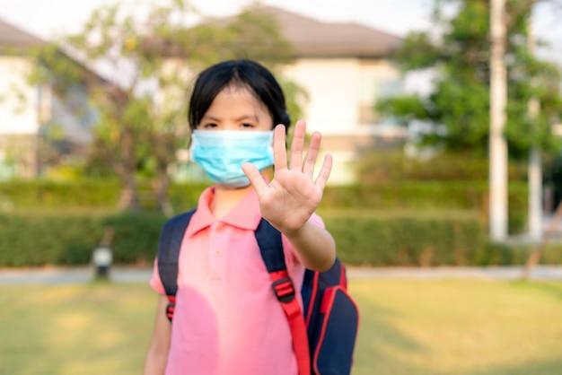 Niña asiática con máscara para proteger pm2.5 y mostrar gesto de detener las manos para detener el brote del virus corona.