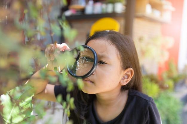 Niña asiática mirando a través de una lupa
