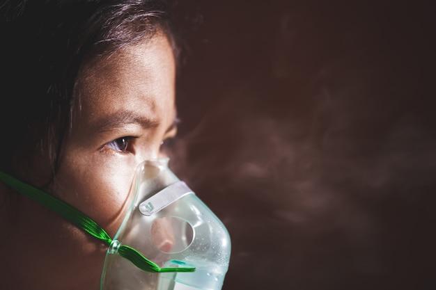 Niña asiática necesita nebulización con una máscara de inhalador en su cara