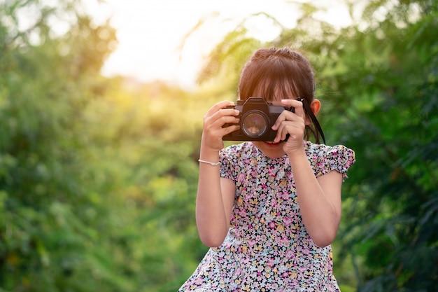 Niña asiática niño con cámara de cine y tomar fotos
