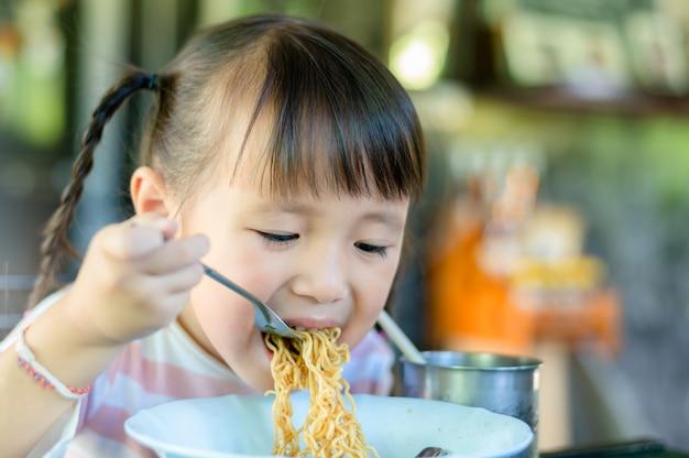 Niña asiática niño comiendo fideos instantáneos en casa