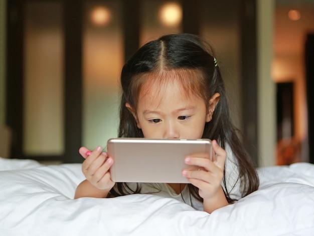 Niña asiática niño mirando teléfono inteligente en la cama