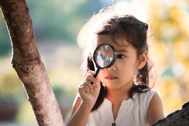 Niña asiática niño mirando a través de una lupa en el árbol en el parque
