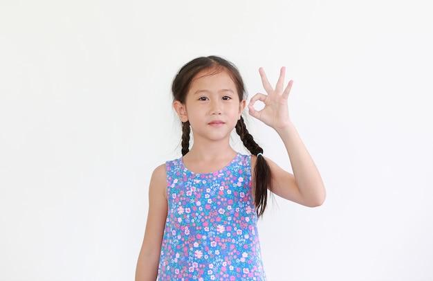 La niña asiática del niño muestra el lenguaje de signos del símbolo bien del dedo aislado en blanco